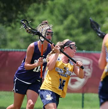 A lacrosse player attempts to score while an opponent defends her