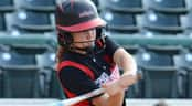 A softball batter swings her bat