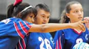 Young Special Olympics athlete receives instruction from volleyball teammate.