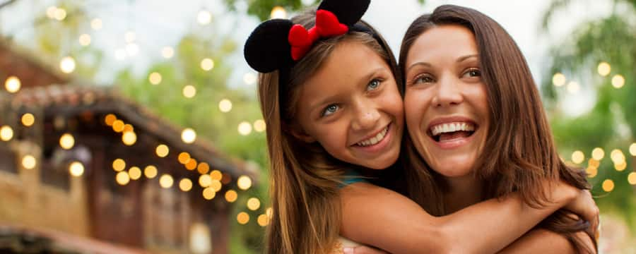 A girl wearing Minnie Ears hugs her mother around the shoulders at Disney's Animal Kingdom park