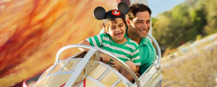 Un père et son fils montent à bord d'une fusée spatiale sur l'AstroOrbiter, une attraction aérienne de type carrousel