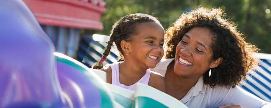 Flotan burbujas junto a un niño que sostiene un globo de Mickey en el parque temático Magic Kingdom