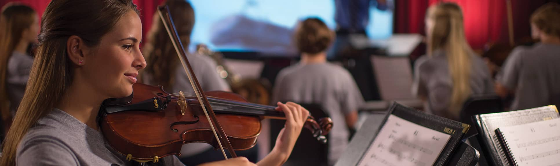 A young girl playing the violin in a room of other musicians led by a conductor