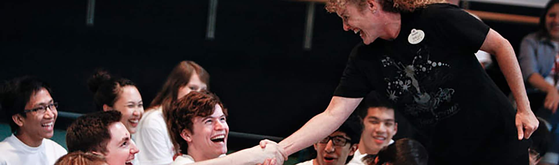A Cast Member shaking hands with a smiling young man