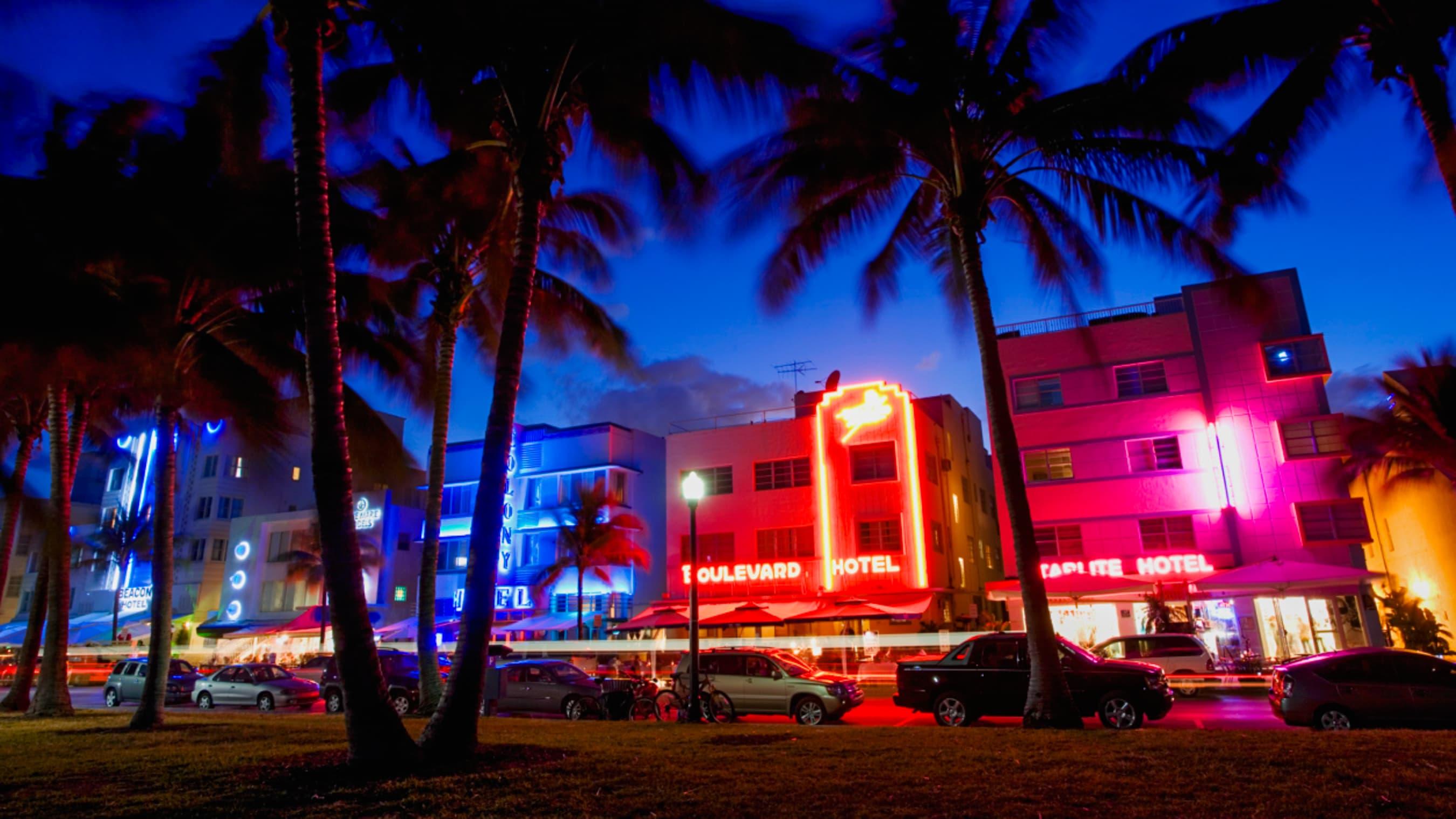 Palmeiras, carros estacionados e hotéis mais intimistas com luzes de neon iluminam a noite em Miami, na Flórida.
