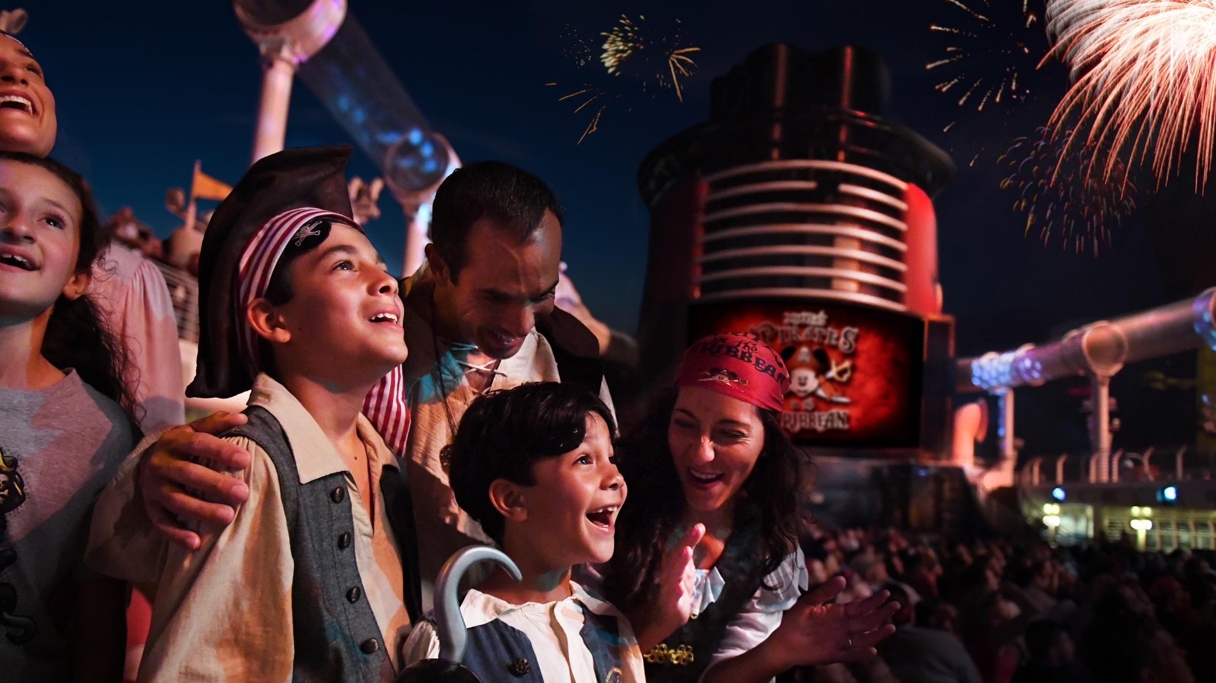Fantasiados de pirata, os integrantes de uma família admiram os fogos de artifício em uma festa no deck da Disney Cruise Line.