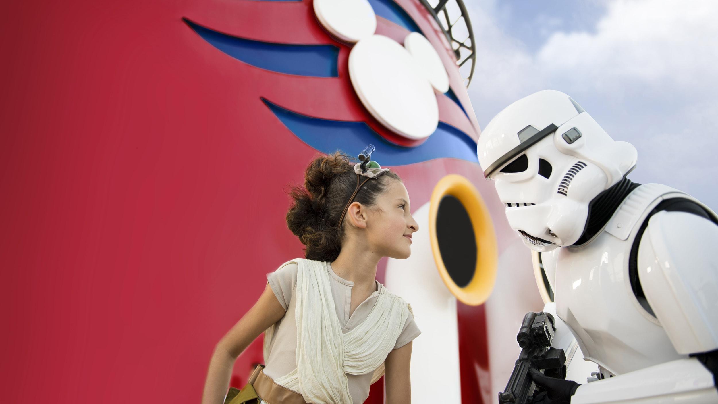Una niñita vestida como Rey de Star Wars, le gruñe a un stormtrooper a bordo de un barco de Disney Cruise Line