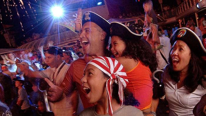 Una familia vestida de piratas se asombra con el cielo iluminado de fuegos artificiales