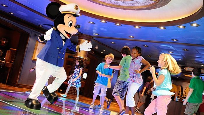 Fantasiado de capitão de navio, Mickey Mouse dança com várias crianças.