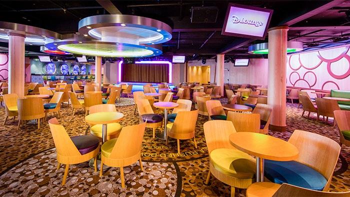 Un salón lleno de sillas y pequeñas mesas redondas incluye una lámpara con un Mickey enorme oculto