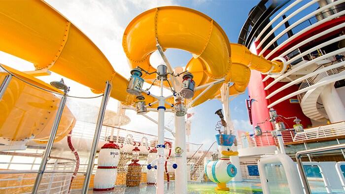 Un tobogán tubular de agua se curva sobre un área de recreación al aire libre en el barco