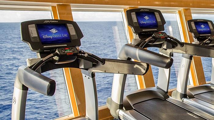 3 caminadoras en un gimnasio tienen vista al mar a través de las ventanas
