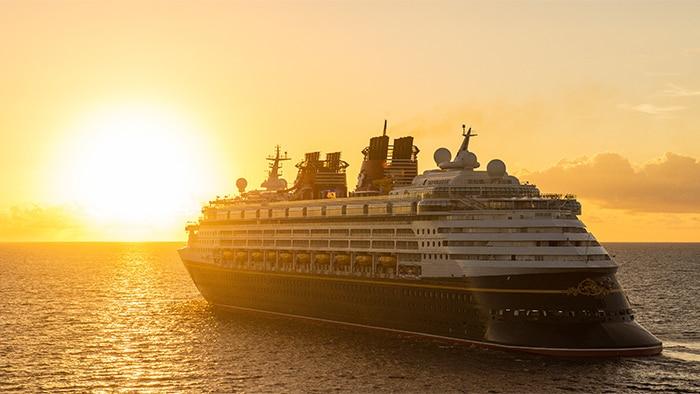 Um navio da Disney Cruise Line navega em direção ao pôr do sol