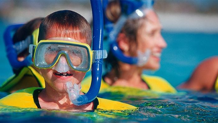 Um garoto faz uma pausa no mergulho de snorkel e posa para uma foto usando máscara.