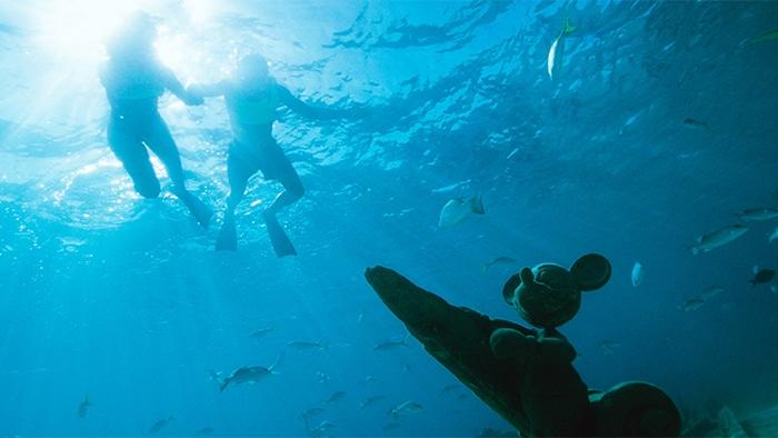 2 buzos con snórkel sumergidos, viendo abajo una estatua de Mickey Mouse con peces nadando alrededor