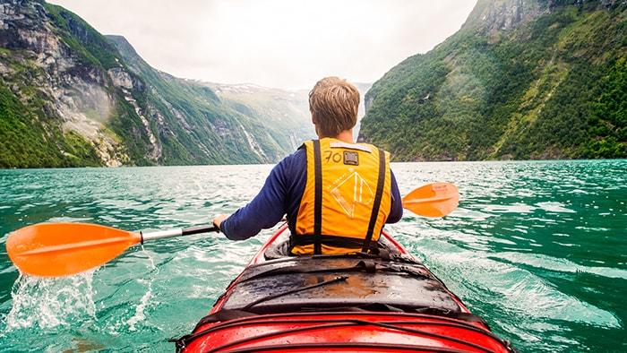 Un hombre rema un kayak hacia una curva en la ensenada