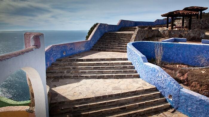 Una amplia escalera de piedra, con descanso cada 5 escalones, lleva a un pabellón tras el cual se puede ver la costa