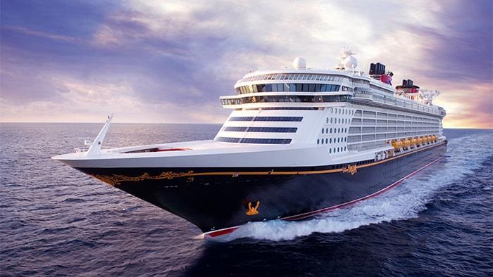 O Disney Dream, um navio com vários andares de altura, em alto-mar, deixando um rastro de espuma.
