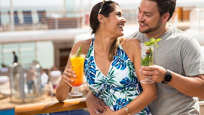 Um casal saboreia coquetéis tropicais no deck