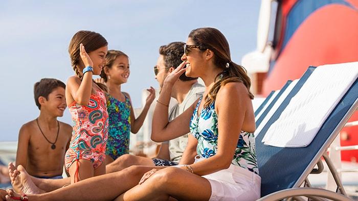 Una mamá y su hija chocan manos en una terraza del barco, con su familia al fondo