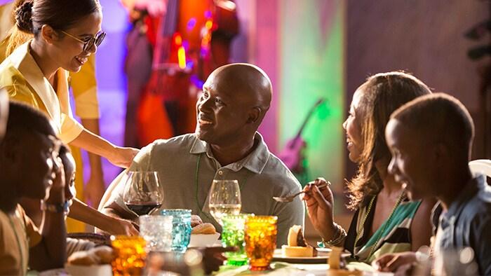 Uma sorridente garçonete atende uma mesa com uma família de cinco pessoas.