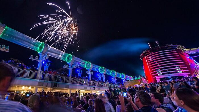 Una multitud toma fotos de los formidables fuegos artificiales que brillan sobre las luces de neón de una cubierta del barco en la noche