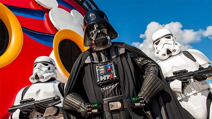 Darth Vader, flanqueado por 2 stormtroopers, se pone en pose amenazadora frente al logotipo de Disney Cruise Line