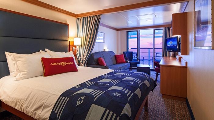 Une cabine avec un très grand lit, un canapé, des chaises, un balcon, une vue d'un coucher de soleil
