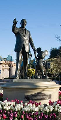 A statue of Walt Disney and Mickey Mouse holding hands, located near Sleeping Beauty Castle