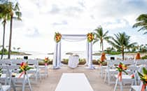 Floral arrangements adorn a wedding altar on a patio overlooking the ocean