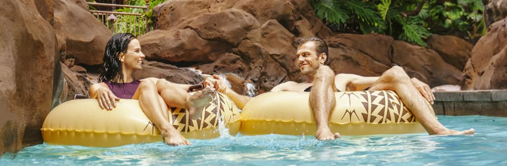 A man and a woman hold hands while floating in inner tubes