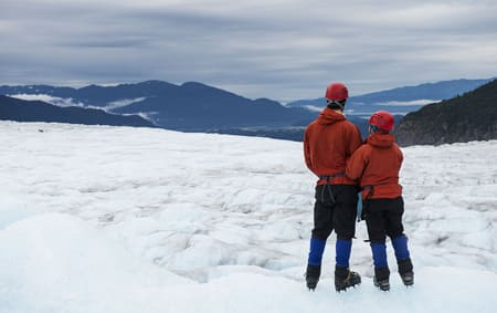 A couple suited up in mountaineering gear stand on an ice field enjoying the Alaskan expanse