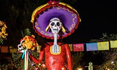 Three Dia de los Muertos calacas are posed with instruments amidst trees and potted flowers
