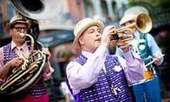 Trumpet player and jazz band in a parade during the New Orleans Bayou Bash and Mardi Gras event