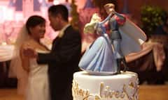 Bride and Groom Dance in View of Cake Topper of Cinderella Dancing with Her Prince