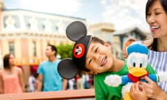 Mother smiles at her son wearing Mickey Ears who is holding a Donald Duck plush toy