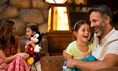A young girl sits in her father's lap in the lobby of their Disney Resort hotel