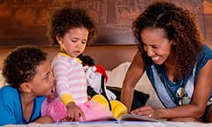 A mother and her little boy and little girl relax in their Disney Resort hotel room and read a picture book together on the bed featuring a headboard with a woodcarving of a fireworks show over Cinderella Castle
