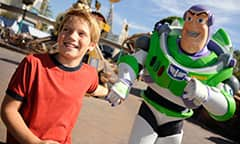 A boy leads Buzz Lightyear away from Tomorrowland