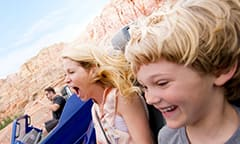 A mother and son hold hands as they ride in their car on the Radiator Springs Racers track
