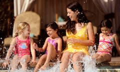 Three young girls and a mother sit on the edge of a pool and splash water around with their feet
