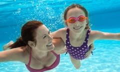 A young girl wearing goggles swims underwater in a Disney Resort hotel pool with her mother