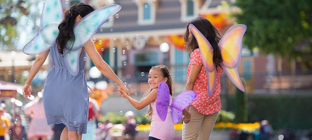 Una mamá, su hija y una amiguita caminan juntas por el parque Disneyland con sus alas de hada.