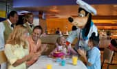 Goofy leads Cast Members and a family in singing happy birthday to a young princess.