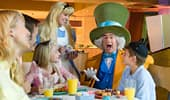 Mad Hatter and Alice entertain a family during breakfast.