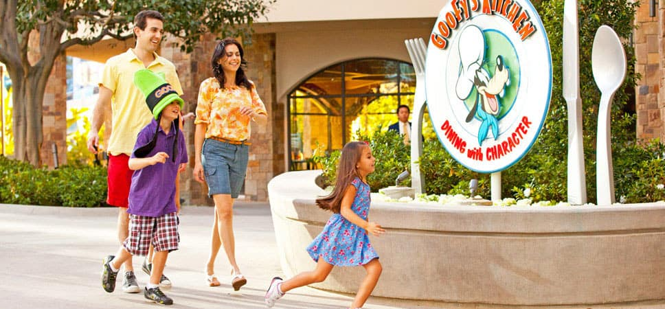 A mom, dad, girl and boy can't wait to enter the Disneyland Hotel restaurant.