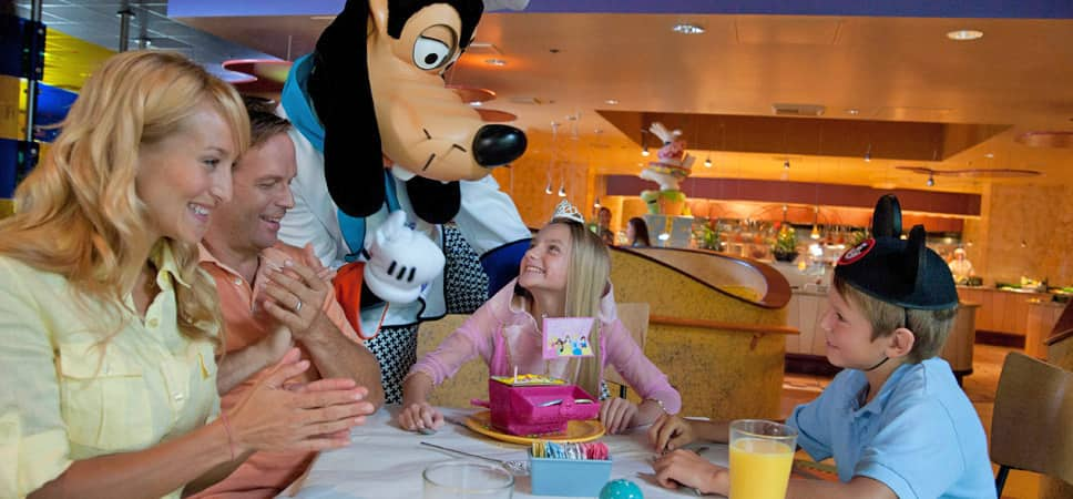 An excited Chef Goofy stops at family's table to share a birthday moment with a young princess.