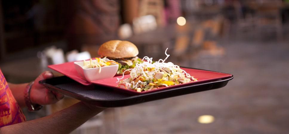Un mesero lleva una charola con hamburguesa, ensalada y acompañamiento.