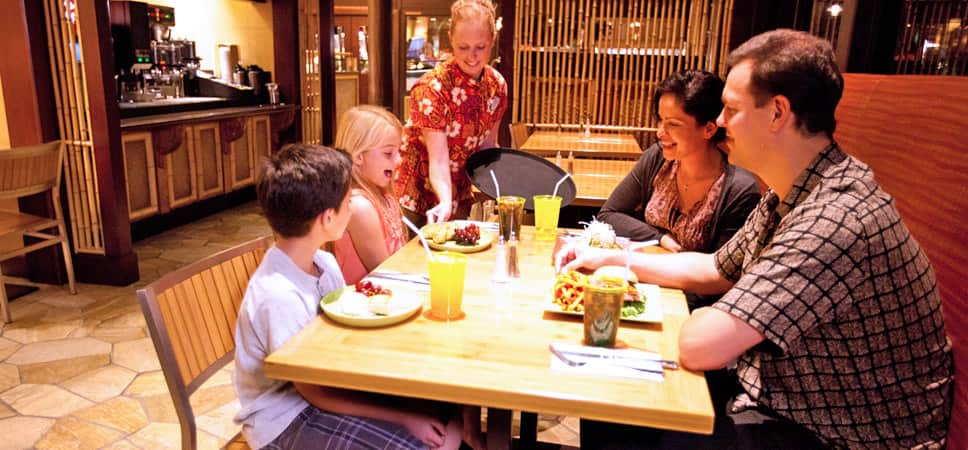 A family, seated inside the restaurant, is served fresh fare.