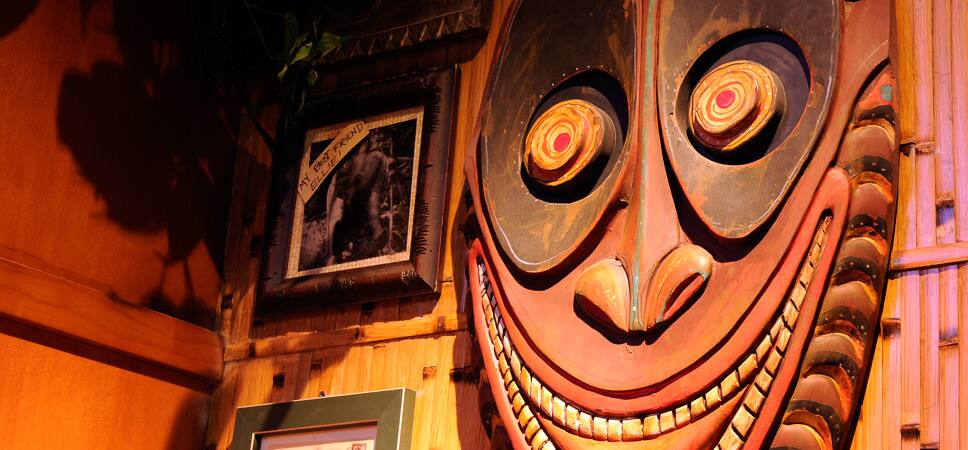 Wall hangings of a giant tiki mask, framed photos and handwritten notes.